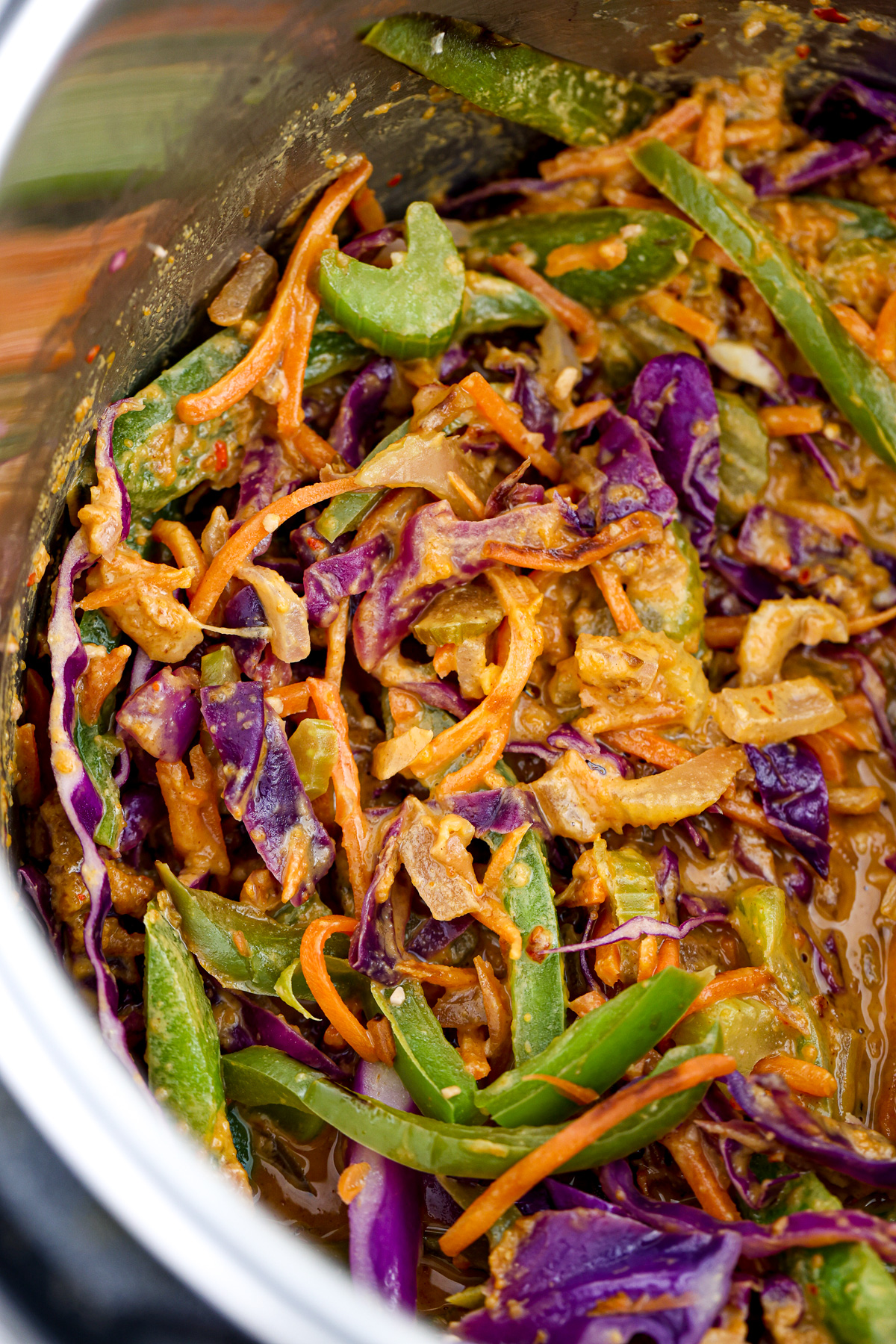 Mixed veggies with celery, green bell peppers, cabbage and peanut sauce in a metal instant pot.