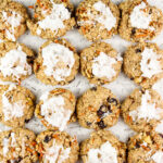 Picture of white backdrop with carrot cake cookies staggered on top.
