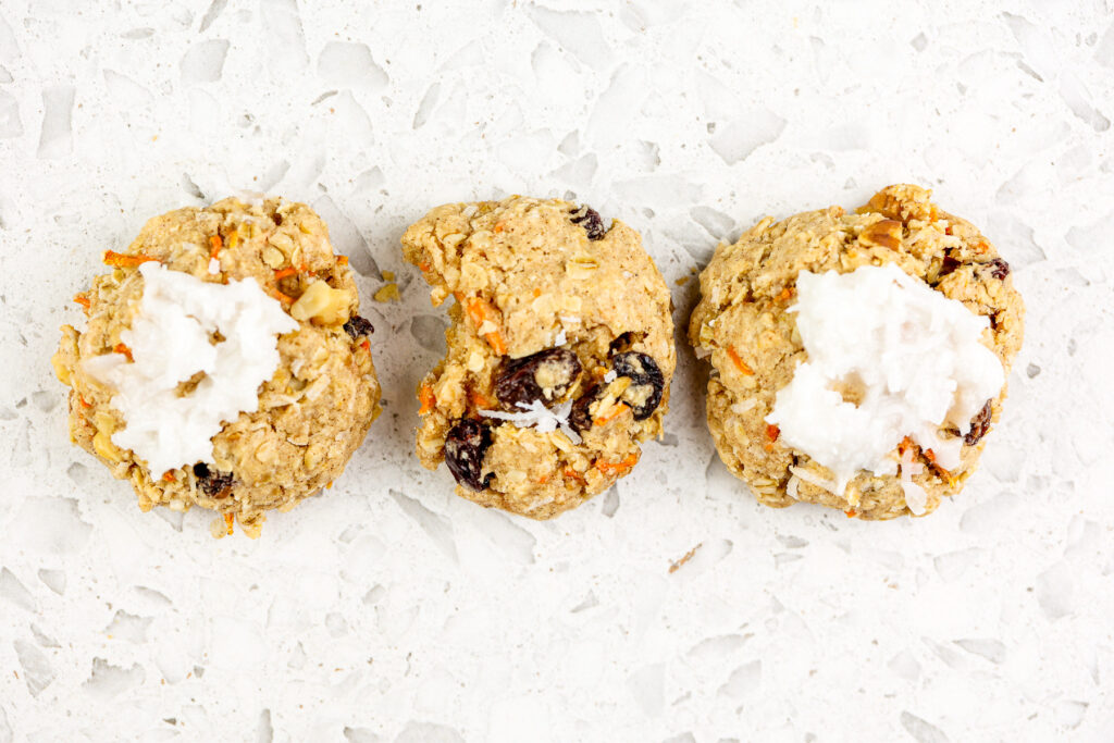 White marble backdrop with single cookie on top with one bite out of it.