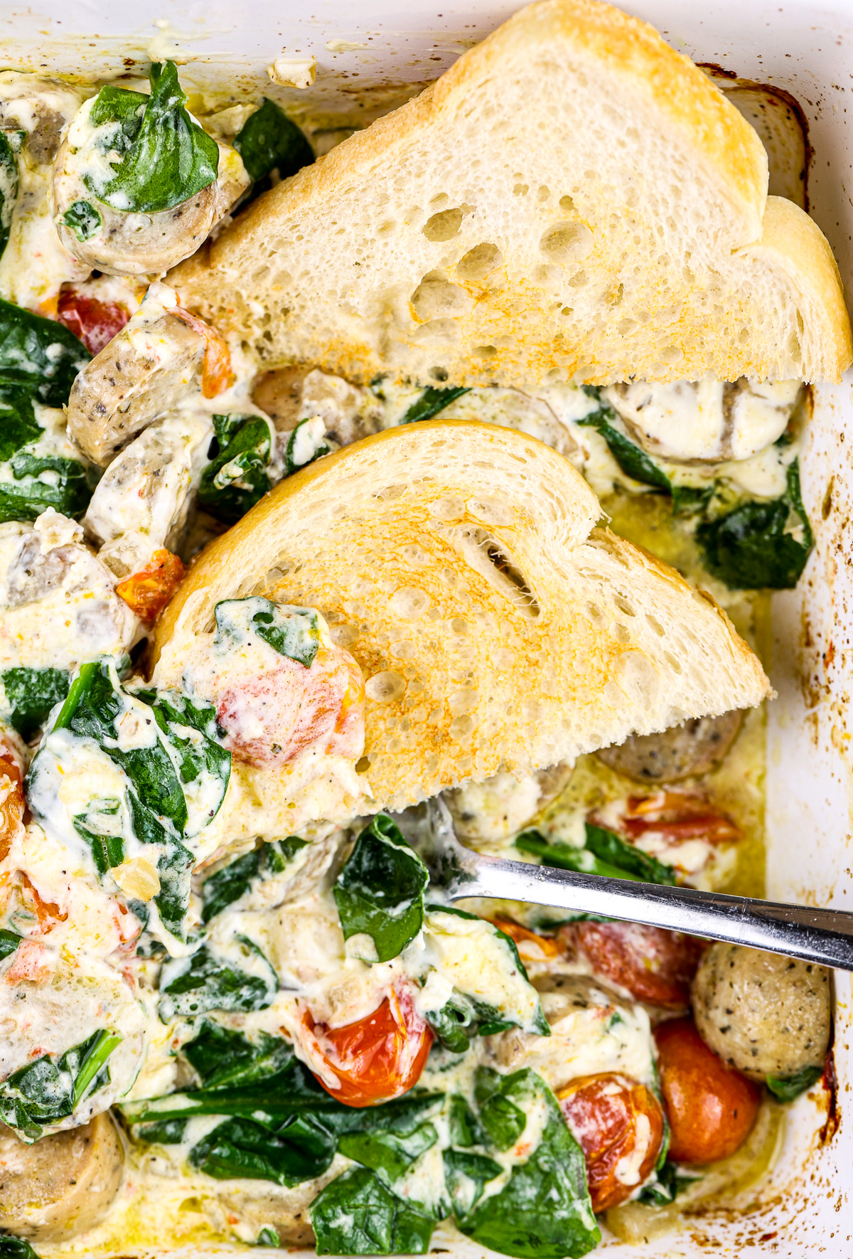 White backdrop with casserole dish filled with creamy white sauce, sausage, and tomatoes with cooked spinach and sliced bread.