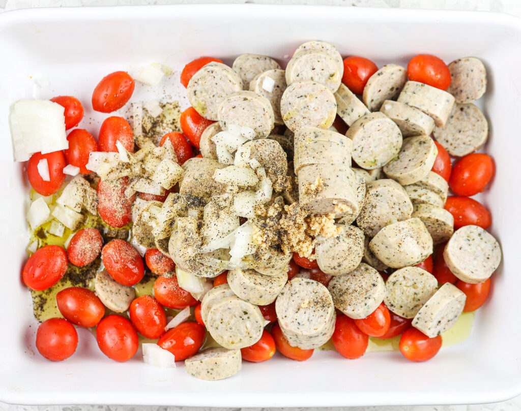 White casserole dish with tomatoes, sausage, and spices.