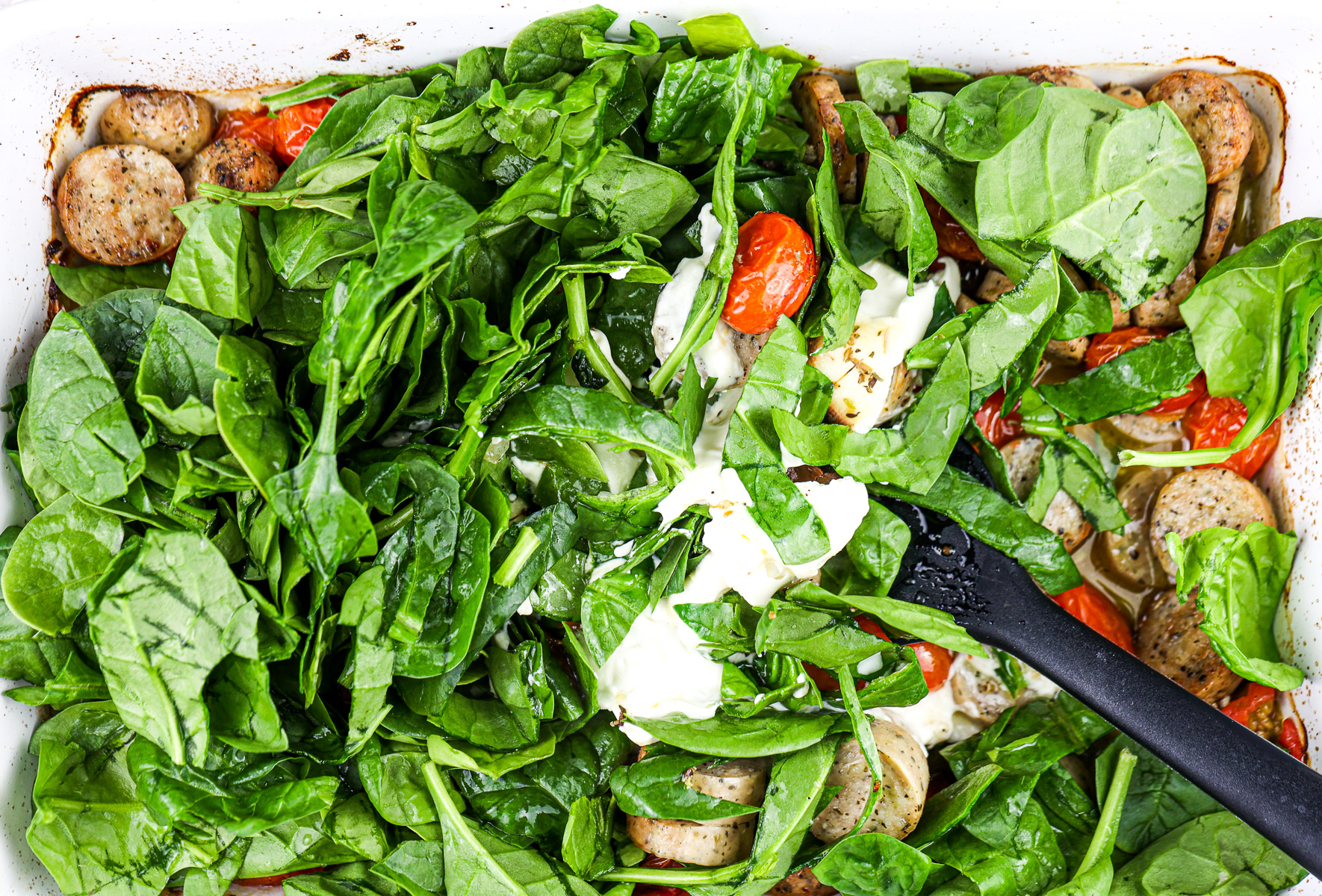 Bed of spinach with spatula mixing it into casserole dish.