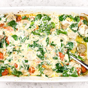 White backdrop with casserole dish filled with creamy white sauce, sausage, and tomatoes with cooked spinach.