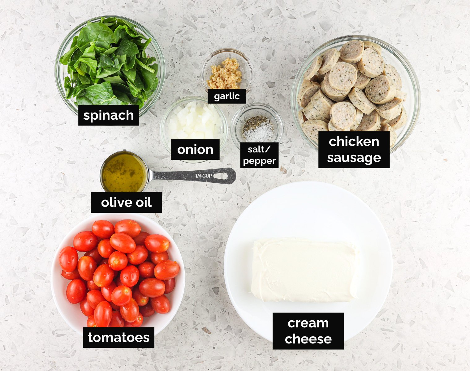White backdrop with ingredient bowls containing spinach, sausage, spices, and cheese to make casserole with black labels.