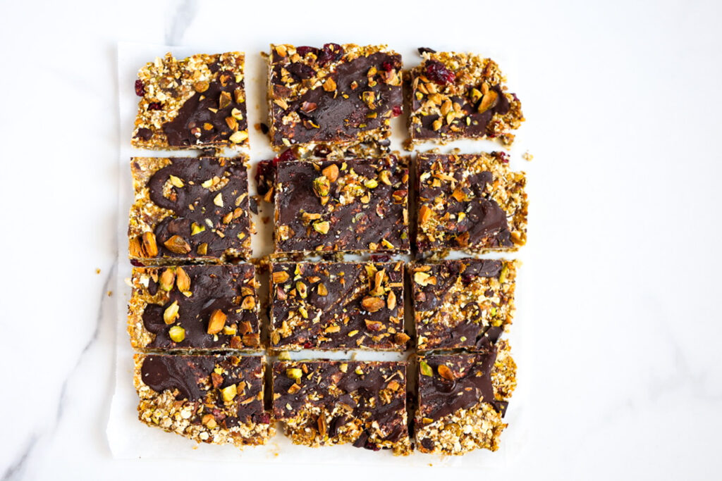Pistachio No Bake Snack Bars cut into squares on white backdrop.