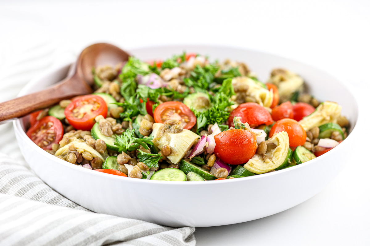 Large salad bowl with lentil salad against white backdrop with wooden spoon.