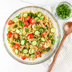 Pasta salad in white bowl with wooden spoon.