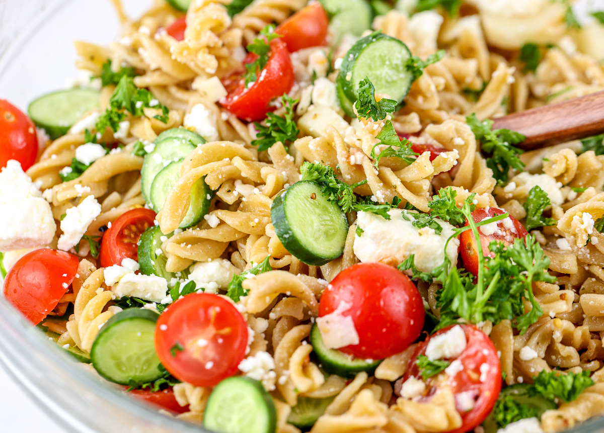 Close up shot of whole grain pasta tossed with veggies for Mediterranean Pasta Salad.