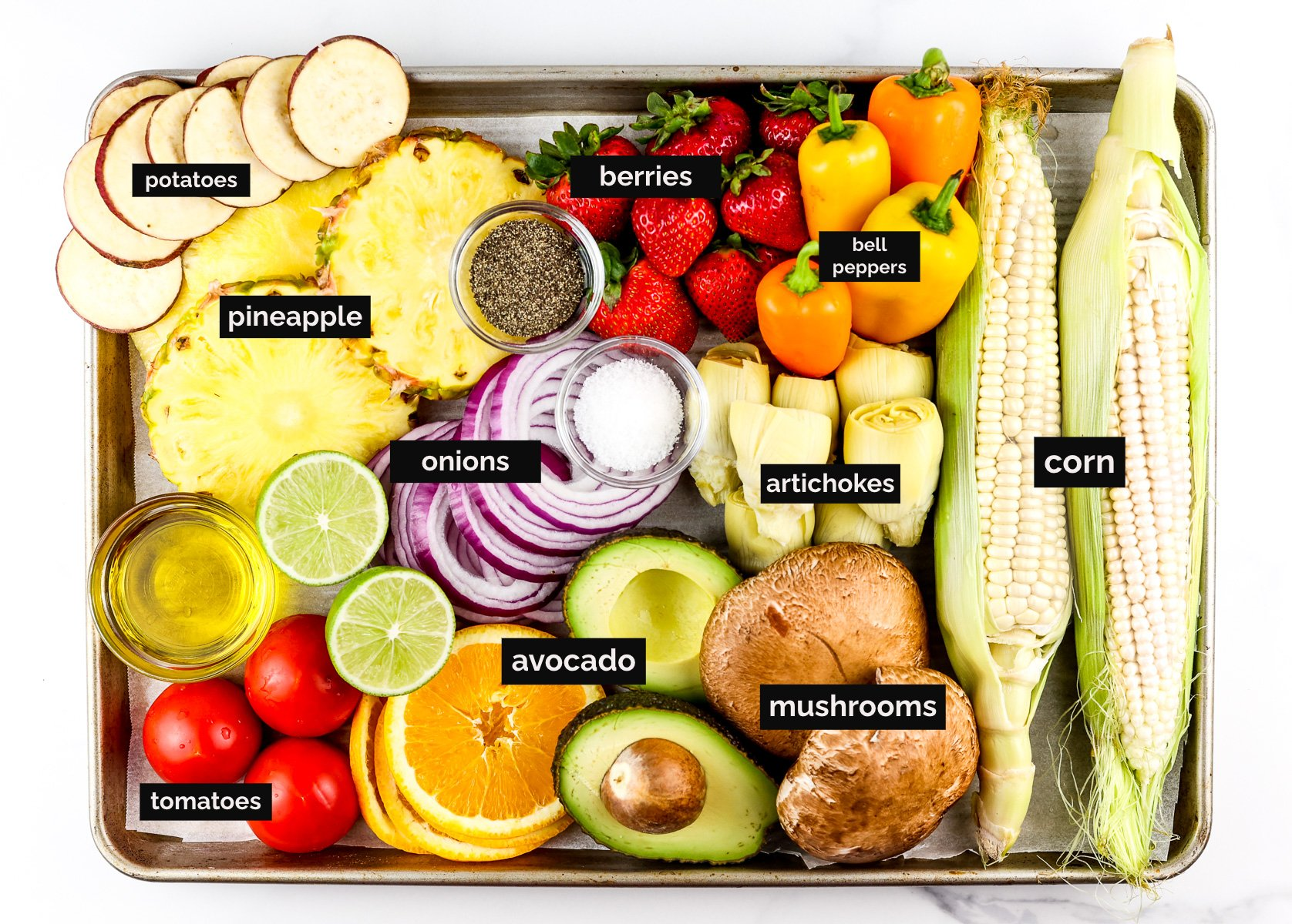 Baking sheet filled with a variety of produce.