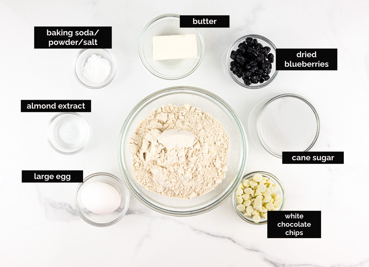 Ingredients laid out on white backdrop to make blueberry cookies.