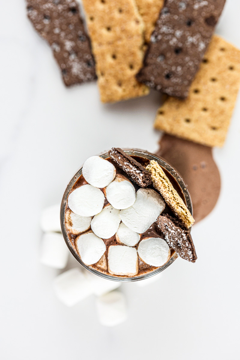 Chocolate S'mores Milkshake with ice cream melting over cup onto white background.