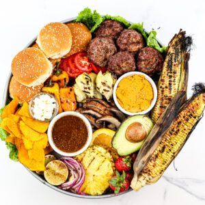 White marble backdrop with beef burgers and fixings on a board.