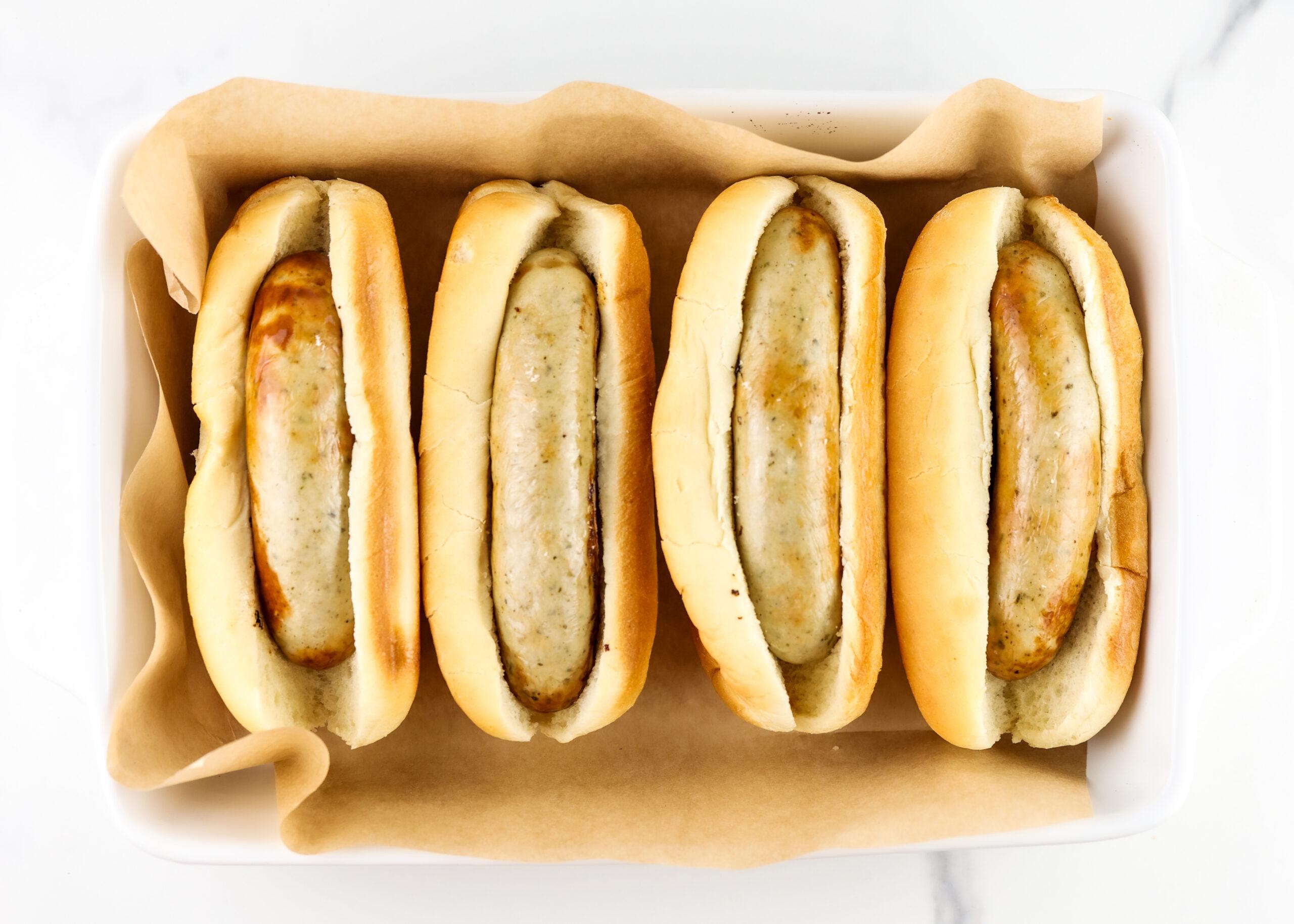 Air fryer bratwurst in buns in a casserole dish.