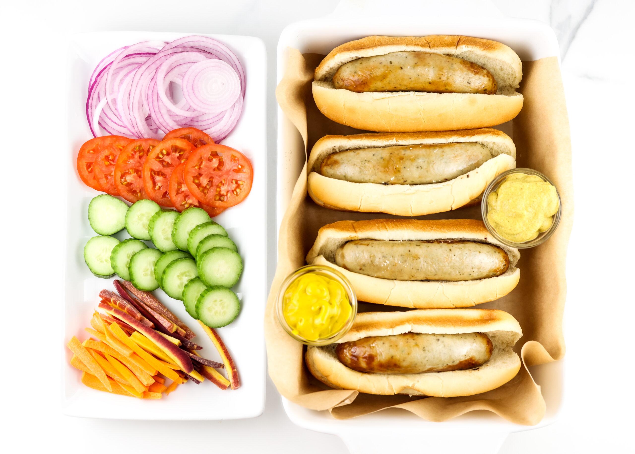 Bratwurst in buns, on a platter, alongside veggie toppings.