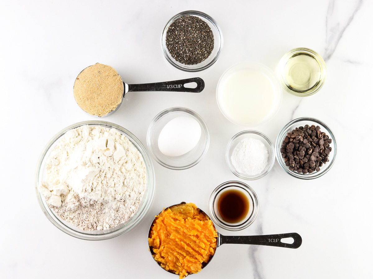 White marble backdrop with ingredients to make muffins on top.