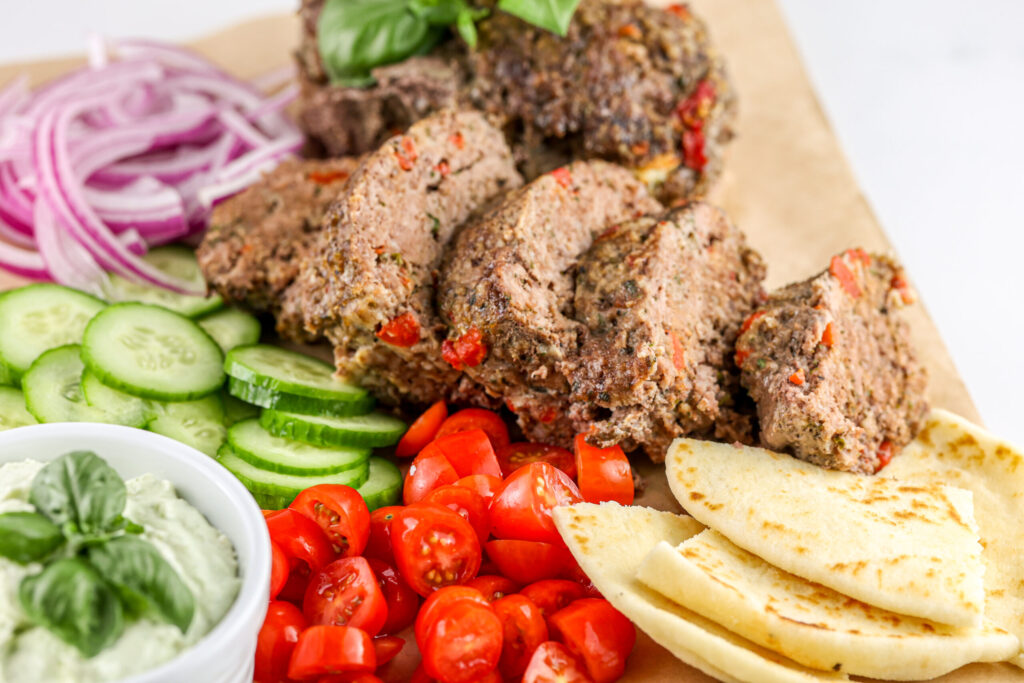 Air fryer meatloaf sliced thin with gyro toppings.