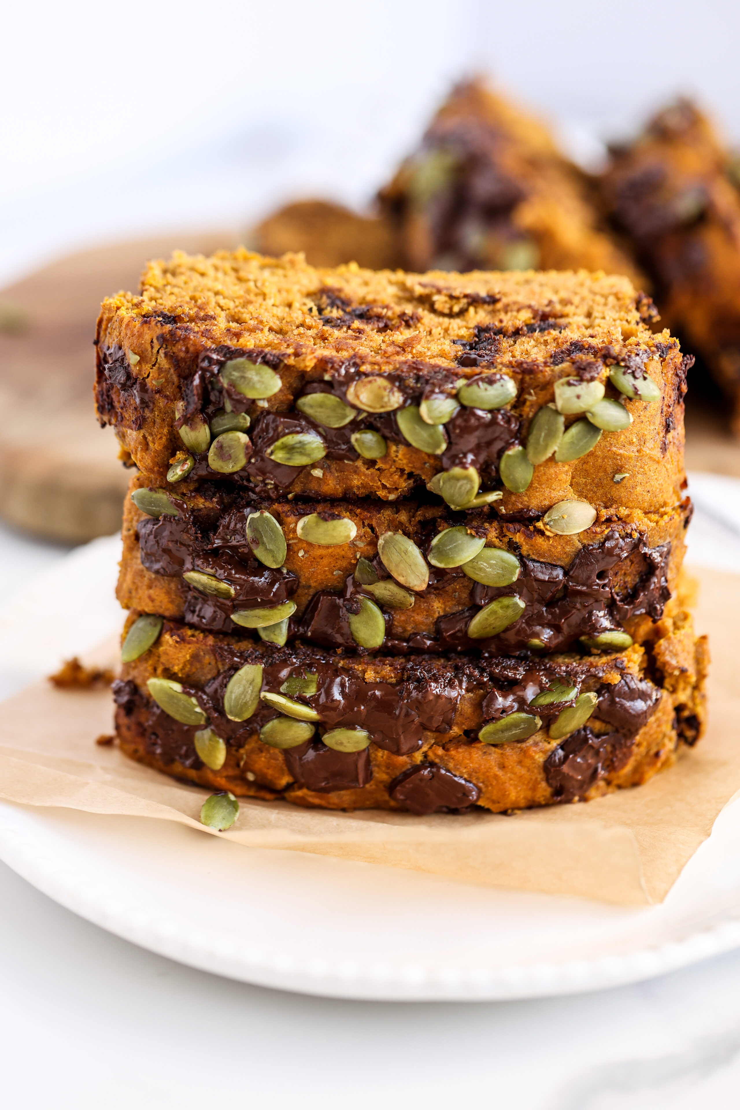 Three slices of pumpkin bread stacked on a piece of brown paper.